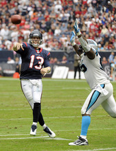 Houston Texans quarterback T.J. Yates (13) throws a pass under pressure from Carolina Panthers defensive end Charles Johnson (95)during the third quarter of an NFL football game on Sunday, Dec. 18, 2011, in Houston. (AP Photo/Dave Einsel)