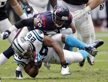 Carolina Panthers running back Jonathan Stewart (28) is tackled by Houston Texans strong safety Glover Quin (29) in the second quarter of an NFL football game on Sunday, Dec. 18, 2011, in Houston. (AP Photo/David J. Phillip)