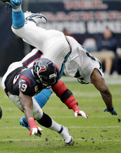 Houston Texans inside linebacker DeMeco Ryans (59) upends Carolina Panthers running back Jonathan Stewart in the second quarter of an NFL football game on Sunday, Dec. 18, 2011, in Houston. (AP Photo/David J. Phillip)