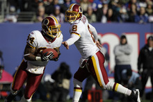 Washington Redskins quarterback Rex Grossman, right, hands the ball to Niles Paul during the first quarter of an NFL football game against the New York Giants, Sunday, Dec. 18, 2011, in East Rutherford, N.J. (AP Photo/Kathy Willens)