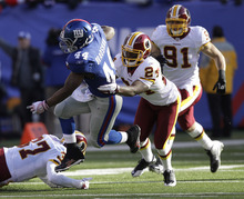 Washington Redskins' DeJon Gomes, second from right, tackles New York Giants' Ahmad Bradshaw, second from left, during the first quarter of an NFL football game on Sunday, Dec. 18, 2011, in East Rutherford, N.J. (AP Photo/Kathy Willens)