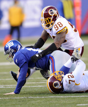 Washington Redskins' Brian Orakpo, top, jumps on New York Giants' Eli Manning, center, after Manning was sacked by Redskins' Stephen Bowen, bottom, during the third quarter of an NFL football game on Sunday, Dec. 18, 2011, in East Rutherford, N.J.  (AP Photo/Bill Kostroun)