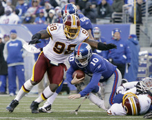Washington Redskins' Brian Orakpo, left, jumps on New York Giants' Eli Manning, center, after Manning was sacked by Redskins' Stephen Bowen, bottom right, during the third quarter of an NFL football game on Sunday, Dec. 18, 2011, in East Rutherford, N.J. (AP Photo/Kathy Willens)