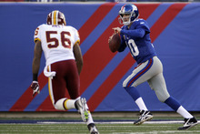 New York Giants quarterback Eli Manning (10) runs as Washington Redskins inside linebacker Perry Riley (56) pursues him during the first quarter of an NFL football game, Sunday, Dec. 18, 2011, in East Rutherford, N.J. (AP Photo/Julio Cortez)