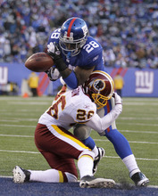 New York Giants' D.J. Ware, top, bobbles the ball while being tackled by Washington Redskins' Josh Wilson on the goal line during the fourth quarter of an NFL football game on Sunday, Dec. 18, 2011, in East Rutherford, N.J. Ware caught the ball and it was called a touchdown but upon review the call was reversed. (AP Photo/Julio Cortez)