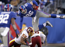 New York Giants' Bear Pascoe, top, leaps over Washington Redskins defenders during the fourth quarter of an NFL football game on Sunday, Dec. 18, 2011, in East Rutherford, N.J. The Redskins defeated the Giants 23-10. (AP Photo/Julio Cortez)