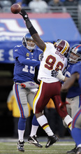 Washington Redskins' Brian Orakpo, right, tries to get a hand on a pass from New York Giants' Eli Manning during the third quarter of an NFL football game on Sunday, Dec. 18, 2011, in East Rutherford, N.J. (AP Photo/Kathy Willens)