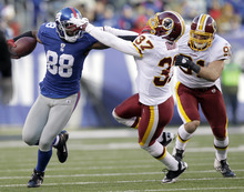 New York Giants' Hakeem Nicks, left, tries to get away from Washington Redskins' Reed Doughty, center, and  Lorenzo Alexander during the third quarter of an NFL football game on Sunday, Dec. 18, 2011, in East Rutherford, N.J. (AP Photo/Kathy Willens)