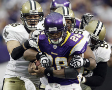 Minnesota Vikings running back Adrian Peterson (28) is stopped by New Orleans Saints' Scott Shanle (58),  Will Smith (91) and  Tom Johnson during the second half of an NFL football game Sunday, Dec. 18, 2011, in Minneapolis. (AP Photo/Morry Gash)