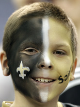 A New Orleans Saints fan watches players warm up before an NFL football game against the Minnesota Vikings Sunday, Dec. 18, 2011, in Minneapolis. (AP Photo/Charlie Neibergall)