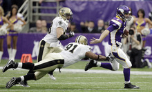 Minnesota Vikings quarterback Christian Ponder (7) runs past New Orleans Saints' Will Smith (91) and  Scott Shanle (58) during the first half of an NFL football game Sunday, Dec. 18, 2011, in Minneapolis. (AP Photo/Charlie Neibergall)