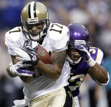 New Orleans Saints' Robert Meachem (17) catches a pass in front of Minnesota Vikings' Jamarca Sanford during the first half of an NFL football game Sunday, Dec. 18, 2011, in Minneapolis. (AP Photo/Charlie Neibergall)