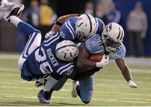 Tennessee Titans running back Chris Johnson (28) is tackled by Indianapolis Colts cornerback Chris Rucker (36) and linebacker Ernie Sims during the second quarter of an NFL football game in Indianapolis, Sunday, Dec. 18, 2011. (AP Photo/Darron Cummings)