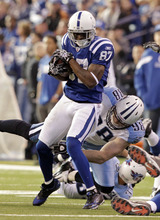 Indianapolis Colts wide receiver Reggie Wayne , top, is tacked by Tennessee Titans defensive end Dave Ball after picking up seven yards during the first quarter of an NFL football game in Indianapolis, Sunday, Dec. 18, 2011. (AP Photo/AJ Mast)
