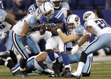 Indianapolis Colts running back Joseph Addai, center, is tackled by Tennessee Titans defenders Derrick Morgan, left, Ken Amato, right center, and Alterraun Verner during the second quarter of an NFL football game in Indianapolis, Sunday, Dec. 18, 2011. (AP Photo/AJ Mast)