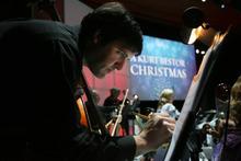 Kim Raff | The Salt Lake Tribune Freelance bass player Ben Henderson celebrates the busiest music season of the year at rehearsal for Kurt Bestor's Christmas concert at Abravanel Hall in Salt Lake City on Thursday, Dec. 8, 2011.