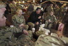 British Prime Minister David Cameron, center, meets with British soldiers at Kandahar airfield, Afghanistan, Tuesday, Dec. 20, 2011. Cameron is holding talks with troops in southern Afghanistan amid discussions over how international forces plan to meet their 2014 deadline to withdraw from combat. (AP Photo/Jeff J. Mitchell, Pool)