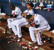 Atlanta Braves, from left, Cristhian Martinez, Alex Gonzalez and Martin Pardo sit on the bench after the Braves' 4-3 loss to the Philadelphia Phillies in 13 innings in a baseball game in Atlanta on Wednesday, Sept. 28, 2011. The loss and the St. Louis Cardinals' win ended the Braves' season. (AP Photo/John Bazemore)