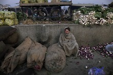 Pakistani Mohammed Nazir, 71, sits on the ground wrapping himself with a shawl to avoid the morning cold at a market to collect fruits and vegetables left by vendors, on the outskirts of Islamabad, Pakistan, Friday, Dec. 23, 2011. (AP Photo/Muhammed Muheisen)