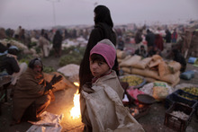 A Pakistani boy looks on at a market collecting fruits and vegetables left by vendors, on the outskirts of Islamabad, Pakistan, in the cold morning Friday, Dec. 23, 2011. (AP Photo/Muhammed Muheisen)