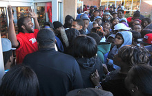 A store employee pleads with a crowd waiting to buy Nike's newly released Air Jordan 11 Retro Concords to