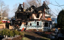 Tina Fineberg  |  The Associated Press Firefighters investigate a house where an early morning fire left five people dead Sunday in Stamford, Conn. Two people escaped.