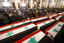 Muzaffar Salman  |  The Associated Press Mourners bow in prayer at a mass funeral Saturday, Dec. 24, 2011 for 44 people killed in twin suicide bombings that targeted intelligence agency compounds in Damascus, Syria. Mourners carried coffins draped in the red, white and black Syrian flags into the eighth-century Omayyad Mosque, where they were placed on the ground for prayers.