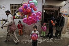 A Pakistani boy holds a balloon after buying it from a vendor on Christmas day in a Christian neighborhood in Islamabad, Pakistan, Sunday, Dec. 25, 2011. (AP Photo/Muhammed Muheisen)