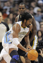 Denver Nuggets center Nene, from Brazil, drives past Utah Jazz forward Paul Millsap during the first quarter of an NBA basketball game Wednesday, Dec. 28, 2011, in Denver. (AP Photo/Jack Dempsey)