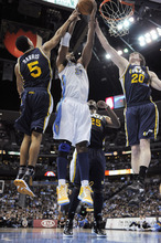 Denver Nuggets center Nene (31), from Brazil, pulls down a rebound against Utah Jazz's Devin Harris (5) and Gordon Hayward (20) during the second quarter of an NBA basketball game Wednesday, Dec. 28, 2011, in Denver. (AP Photo/Jack Dempsey)