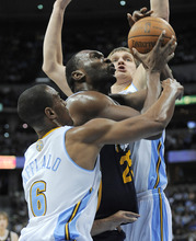 Utah Jazz center Al Jefferson (25) is fouled as he drives between Denver Nuggets' Arron Afflalo (6) and Timofey Mozgov, from Russia, during the first quarter of an NBA basketball game Wednesday, Dec. 28, 2011, in Denver. (AP Photo/Jack Dempsey)