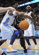 Denver Nuggets center Nene (31), from Brazil ,and Utah Jazz center Al Jefferson (25) go after a loose ball as Nuggets guard Ty Lawson (3) looks on during the second quarter of an NBA basketball game Wednesday, Dec. 28, 2011, in Denver. (AP Photo/Jack Dempsey)