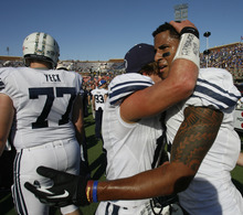 Rick Egan  | The Salt Lake Tribune   Riley Nelson (13) hugs Wide receiver Cody Hoffman (2) as they celebrates the Cougars 24-21 win over Tulsa in the Armed Forces Bowl, in Dallas, Texas, Friday, December 30, 2011