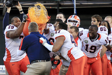 Illinois interim coach Vic Koenning, in blue, is doused after Illinois defeated UCLA 20-14 in the Fight Hunger Bowl NCAA college football game in San Francisco, Saturday, Dec. 31, 2011. (AP Photo/Marcio Jose Sanchez)
