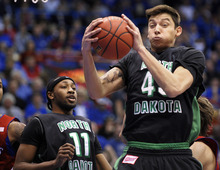 North Dakota forward Patrick Mitchell (45) pulls down a rebound against Kansas in front of guard Jamal Webb (11) during the first half of an NCAA college basketball game in Lawrence, Kan., Saturday, Dec. 31, 2011. (AP Photo/Reed Hoffmann)