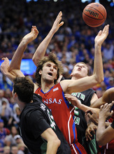 Kansas center Jeff Withey (5) fights for a rebound against North Dakota forward Patrick Mitchell, left, and center Mitch Wilmer (22) during the first half of an NCAA college basketball game in Lawrence, Kan., Saturday, Dec. 31, 2011. (AP Photo/Reed Hoffmann)