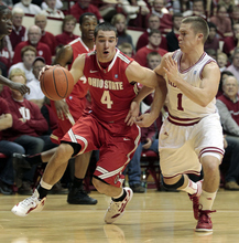Ohio State's Aaron Craft (4) drives to the basket around Indiana's Jordan Hulls during the first half of an NCAA college basketball game on Saturday, Dec. 31, 2011, in Bloomington, Ind. (AP Photo/Darron Cummings)