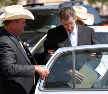 Warren Jeffs, leader of the Fundamentalist Church of Jesus Christ of Latter Day Saints, right, is placed into the back of a waiting car in San Angelo, Texas Tuesday, Aug. 9, 2011. The polygamist leader was sentenced to life in prison for sexually assaulting two underage followers he took as brides in what his church deemed