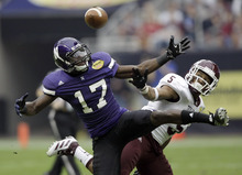 Northwestern wide receiver Rashad Lawrence (17) catches a pass for a first down as Texas A&M defensive back Coryell Judie (5) defends during the first quarter of the Car Care Bowl NCAA college football game Saturday, Dec. 31, 2011, in Houston. (AP Photo/David J. Phillip)