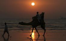 Pakistani youth enjoy a camel ride as the sun sets in Karachi, Pakistan on Saturday, Dec. 31, 2011. (AP Photo/Fareed Khan)