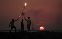 Young Sri Lankan boys play with firecrackers on the eve of the New Year, as the sun sets in Colombo, Sri Lanka, Saturday, Dec. 31, 2011. (AP Photo/ Eranga Jayawardena)