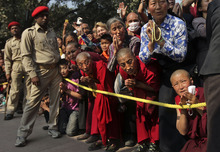Buddhist monks and other devotees wait to welcome their spiritual leader the Dalai Lama upon his arrival in the town of Bodhgaya, believed to be the place where Buddha attained enlightenment, after his arrival for the upcoming Kalachakra Buddhist festival in the eastern Indian state of Bihar, India, Saturday, Dec. 31, 2011.  The Kalachakra, the most important ritual of the Mahayana sect of traditional Buddhists, begins Dec. 31. (AP Photo/Altaf Qadri)