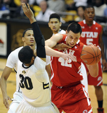 CORRECTS NAME OF UTAH PLAYER - Utah's Jason Washburn (42) tries to drive through Colorado's Carlon Brown during the first half of an NCAA college basketball game, Saturday, Dec. 31, 2011, in Boulder, Colo. (AP Photo/The Daily Camera, Cliff Grassmick) NO SALES; NO MAGS; NO TV