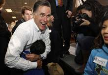 Republican presidential candidate, former Massachusetts Gov. Mitt Romney gets a hug as he campaigns at the Mississippi Valley Fairgrounds in Davenport, Iowa, Monday, Jan. 2, 2012. (AP Photo/Charles Dharapak)