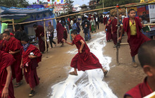 A young Buddhist monk jumps over spilled tea near the venue of the Kalachakra Buddhist festival, in the town of Bodh Gaya, believed to be the place where Buddha attained enlightenment, Bihar, India, Monday, Jan. 2, 2012. (AP Photo/Altaf Qadri)
