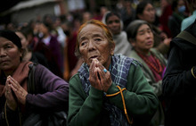 An elderly Buddhist devotee looks at a giant screen on a street, which shows the Kalachakra ritual dance live, during the Kalachakra Buddhist festival, in the town of Bodh Gaya, believed to be the place where Buddha attained enlightenment, Bihar, India, Monday, Jan. 2, 2012. (AP Photo/Altaf Qadri)