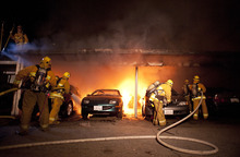 Los Angeles Fire Department firefighters extinguishes numerous cars on fire in a carport in the Sherman Oaks neighborhood of Los Angeles on Monday, Jan. 2, 2012. For the fifth night in a row, a spate of arson fires has sent firefighters scrambling to extinguish car fires in the Hollywood, Hollywood Hills, Studio City, and Sherman Oaks neighborhoods of Los Angeles. The Los Angeles Fire Department confirms a person of interest has been detained and is being questioned in connection with the arson spree. (AP Photo/Dan Steinberg)