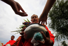 Thai Buddhists offer food to a Buddhist monk during a morning alms at Marble temple in Bangkok Monday, Jan. 2, 2012. (AP Photo/Sakchai Lalait)