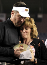 Oklahoma State head coach Mike Gundy, left, hugs Shelley Budke, wife of former Oklahoma State women's basketball coach Kurt Budke who died in a plane crash in 2011, as Gundy presents the Fiesta Bowl Championship Trophy to her after the Fiesta Bowl NCAA college football game Monday, Jan. 2, 2012, in Glendale, Ariz.  Oklahoma State defeated Stanford 41-38 in overtime.(AP Photo/Ross D. Franklin)