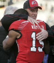 Trent Nelson  |  The Salt Lake Tribune Utah coach Kyle Whittingham embraces running back John White, who was named the game's MVP. The University of Utah faces Georgia Tech, college football at the Sun Bowl in El Paso, Texas, Saturday, December 31, 2011.